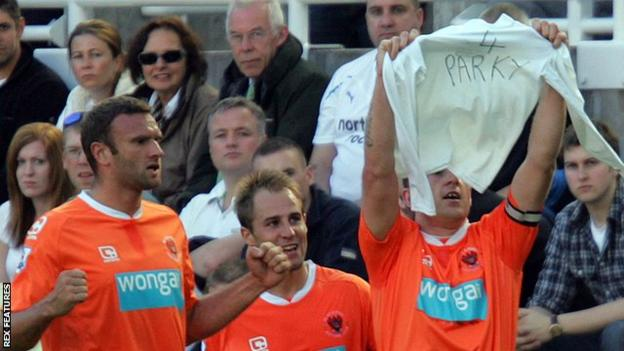 Charlie Adam (right) holds a shirt in dedication to Gary Parkinson after scoring in Blackpool's 2-0 win against Newcastle in September 2010