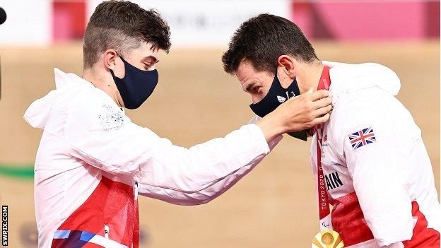 Fin Graham puts Jaco van Gass' gold medal around his neck