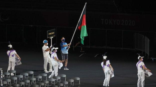 A volunteer carries the Afghanistan flag at the Tokyo National Stadium