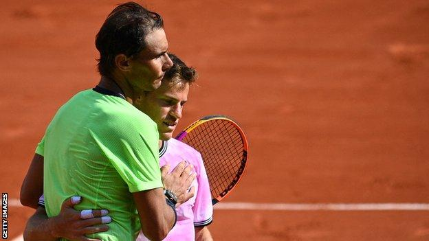 Rafaekl Nadal and Diego Schwartzman hug at the net