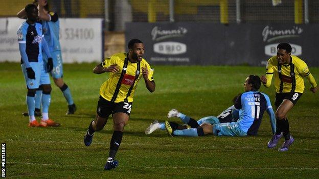 Kevin Lokko of Harrogate Town celebrates after scoring his team's fifth goal against Cambridge United