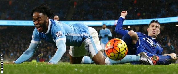 Raheem Sterling tumbles after a challenge from John Stones