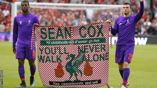 Georginio Wijnaldum and Andrew Robertson carry a flag on the pitch in support of fan Sean Cox