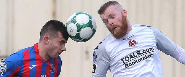 Mark Kelly of Ards in action against Ross Clarke of Crusaders