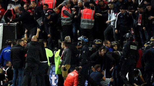 Police and stadium staff help the injured supporters