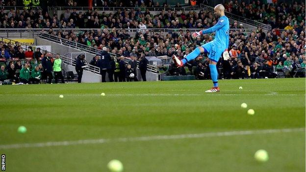 Republic keeper Darren Randolph helps clear the tennis balls from the Aviva pitch