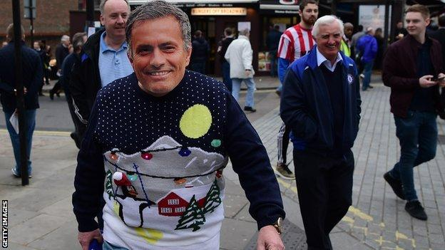 A Chelsea fan wears a Jose Mourinho mask outside Stamford Bridge