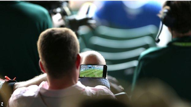 Tennis fan at Wimbledon watching England v Sweden on his phone