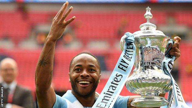 Manchester City's Raheem Sterling lifts the FA Cup