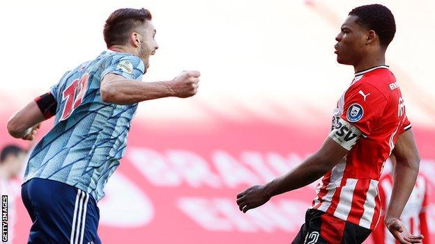 Dusan Tadic of Ajax celebrates his equaliser in front of Denzel Dumfries