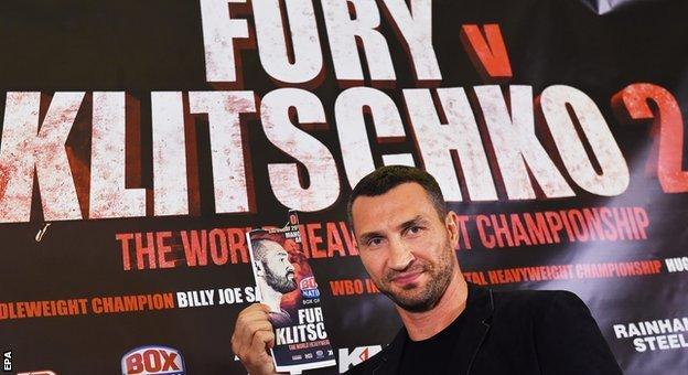 Wladimir Klitschko holds up a poster of Tyson Fury