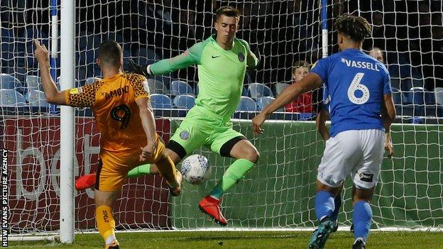 Padraig Amond of Newport County puts the ball past goalkeeper Owen Evans of Macclesfield Town