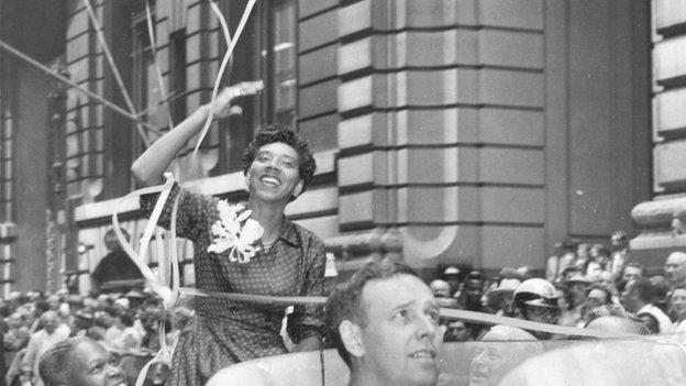 Althea Gibson waves from an open car during a victory parade in New York, 1957.