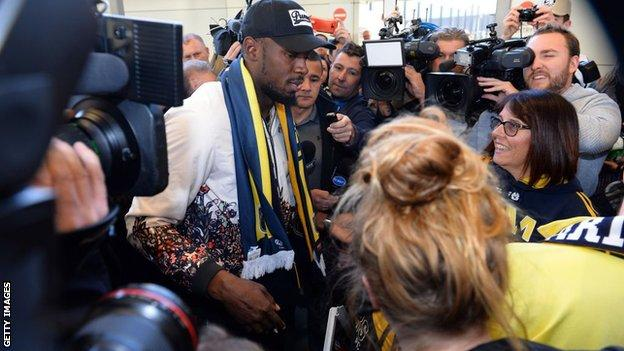 Usain Bolt, wearing a Central Coast Mariners scarf, is surrounded by fans, journalists and photographers after arriving in Sydney for his training period with the A-League side