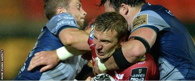 Hadleigh Parkes of Scarlets is tackled by Jack Carty and Denis Buckley