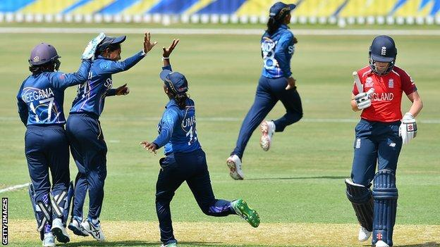 Sri Lanka players celebrate as England's Lauren Winfield walks off the pitch after being run out