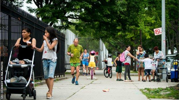 A competitor runs through the crowded sreets of Queens