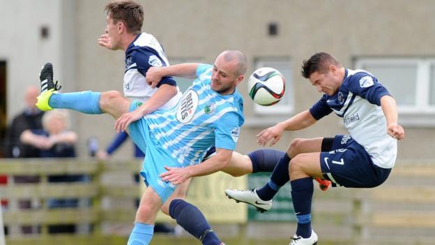 An areial duel between Warrenpoint Town midfielder Stephen Hughes and Ballinamallard United's Liam Martin at Milltown