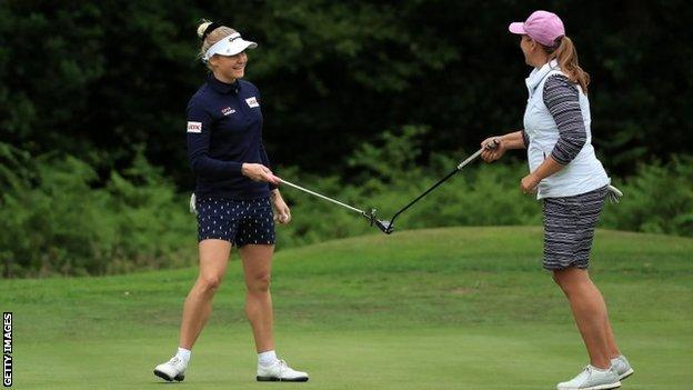Charley Hull (left) and Liz Young touch putters after their play-off at Brockenhurst Manor