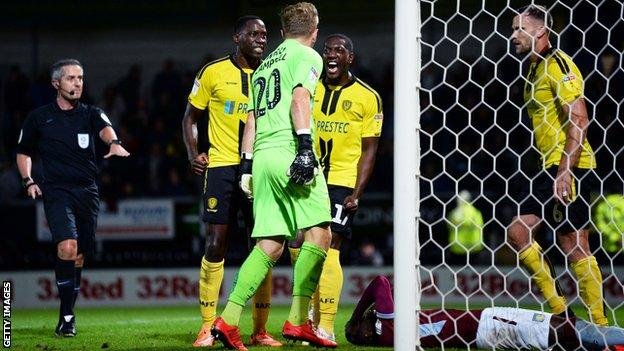 Burton players celebrates as Albert Adomah of Aston Villa penalty is saved by Harry Campbell