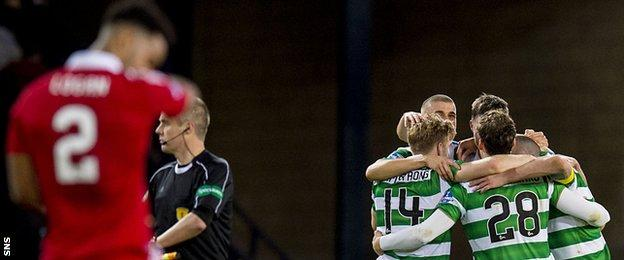 Aberdeen's Shay Logan is left disappointed as Celtic celebrate
