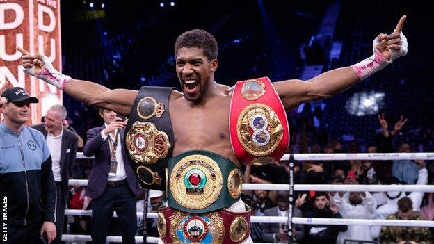 Anthony Joshua celebrates a win with his heavyweight belts