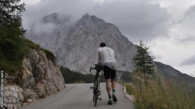 A competitor walks their bike up an extremely steep climb at the Transcontinental race of 2018