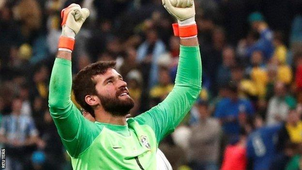 Brazil's Alisson celebrates winning the penalty shootout