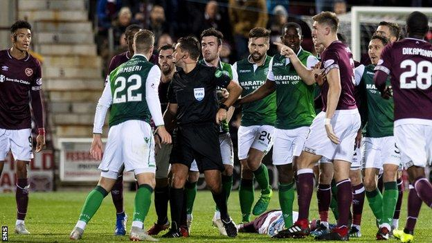 Hearts and Hibernian players with referee Andrew Dallas
