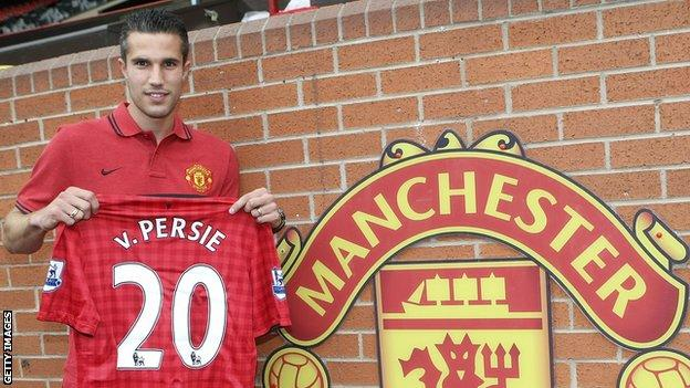 Robin van Persie holds up a Manchester United shirt bearing his name after signing for the club
