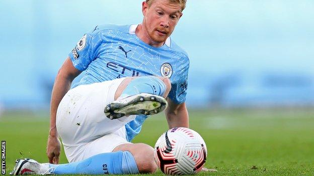 Kevin De Bruyne controls the ball while sat on the pitch