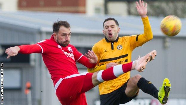 Josh Payne of Crawley Town clears under pressure from Robbie Willmott of Newport County