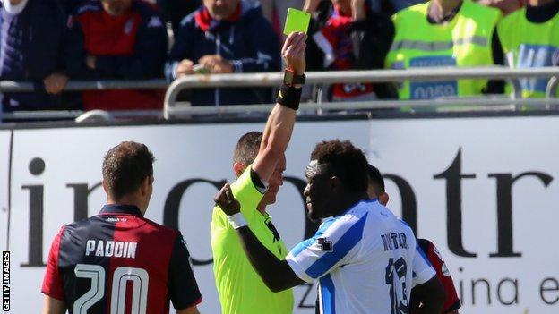 Sulley Muntari is shown a yellow card after he protested against racial abuse