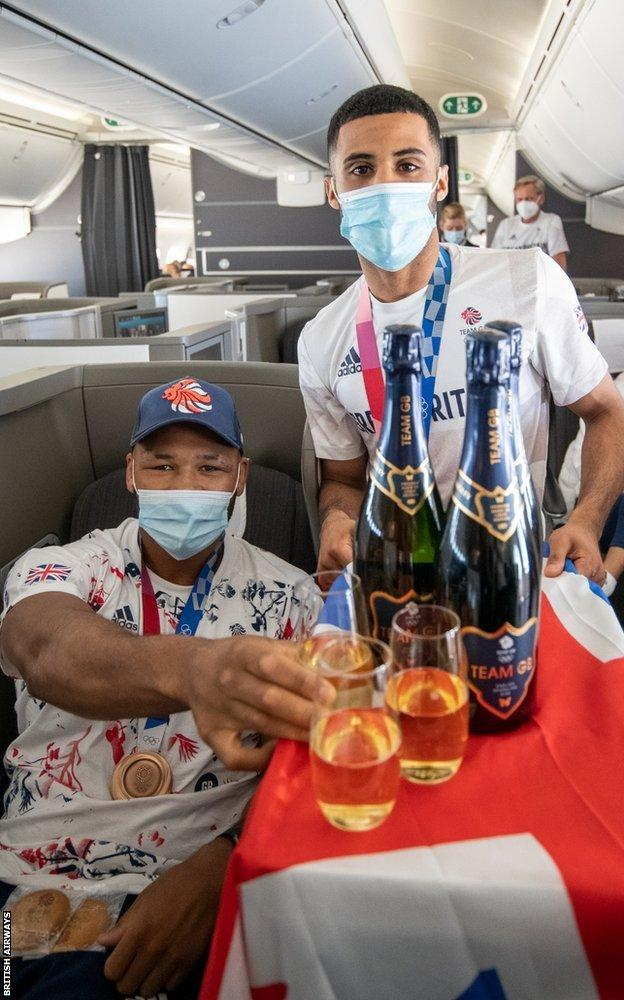 Boxers share drink on flight home from Tokyo 2020.