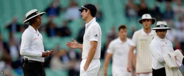 England captain Alastair Cook speaks with the umpires