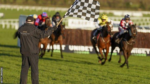 A member of the Cheltenham groundstaff waves a flag to alert jockeys