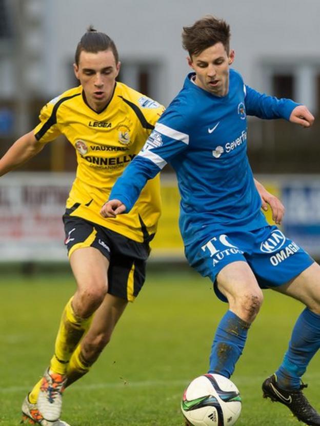 Jamie Glackin of Dungannon moves in to challenge Ballinamallard United's David Elliott during the 1-1 draw in the Irish Premiership