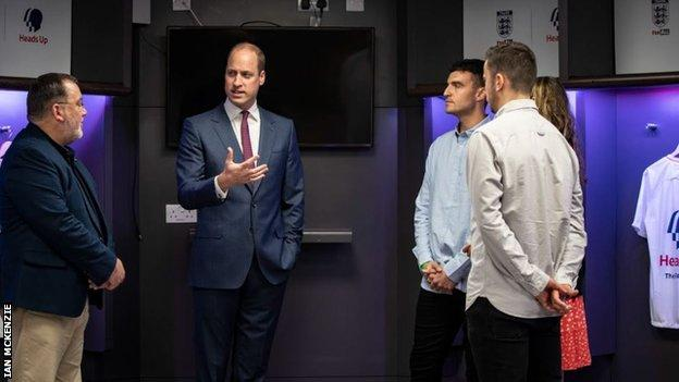 Members of the FC Not Alone club talk with the Duke of Cambridge