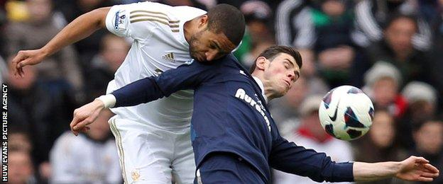 Ashley Williams beats Gareth Bale to the ball during a match between Tottenham and Swansea