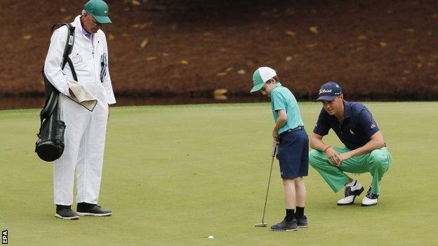 Justin Thomas watches a child hole his putt on the eighth
