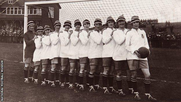 The Dick, Kerr Ladies football team in line on a goal line, with Lily Parr at the front holding a football