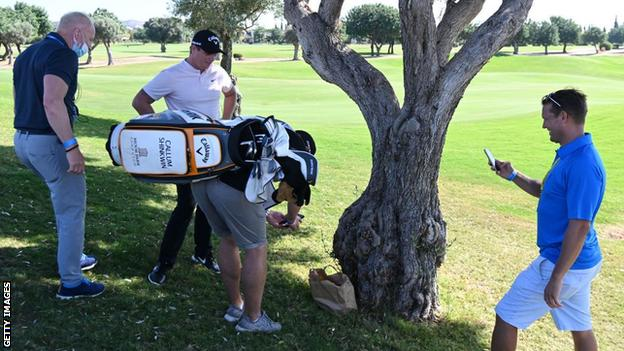 Callum Shinkwin's caddy takes a photo of the ball in the bag