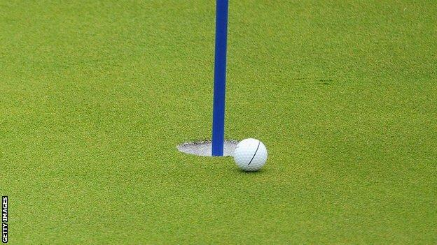 A golf ball going into the hole