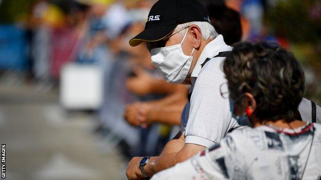 Spectators at a cycling event wearing masks