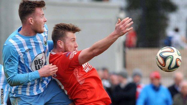 Warrenpoint's Dermot McVeigh challenges Portadown striker Mark McAllister