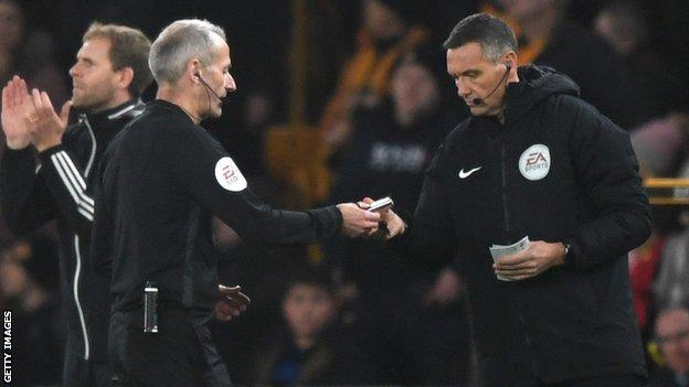Martin Atkinson consults with Andre Marriner