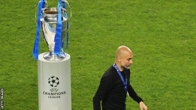 Pep Guardiola walks past the Champions League trophy