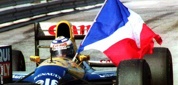 Alain Prost holds his country's flag after clinching his fourth F1 world title at the Portuguese Grand Prix