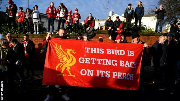 Liverpool fans with a flag saying 'The bird is getting back on its perch'