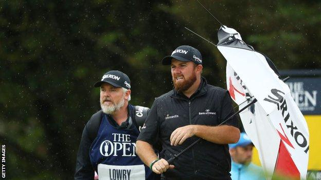 Shane Lowry stands with a broken umbrella